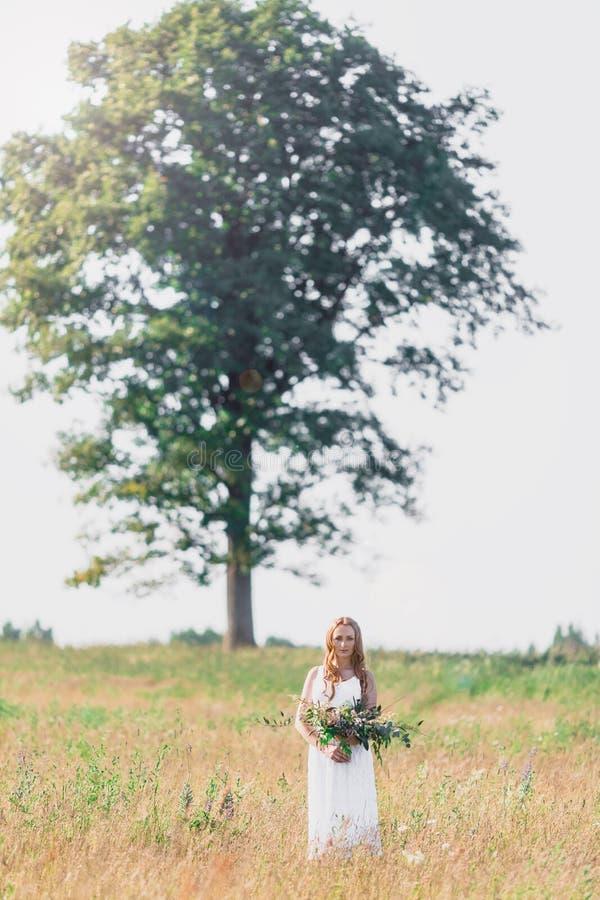 Όμορφη νέα γυναίκα στο υπόβαθρο ενός μεγάλου δέντρου με μια ανθοδέσμη των λουλουδιών στα χέρια τους στοκ φωτογραφία με δικαίωμα ελεύθερης χρήσης
