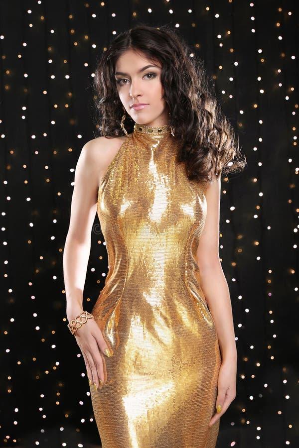 Όμορφη νέα γυναίκα στο χρυσό φόρεμα μόδας πέρα από το φως διακοπών στοκ φωτογραφίες