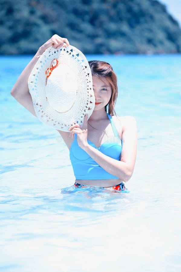 Όμορφη νέα γυναίκα της Ασίας με το καπέλο στο μπικίνι στην παραλία στοκ φωτογραφία