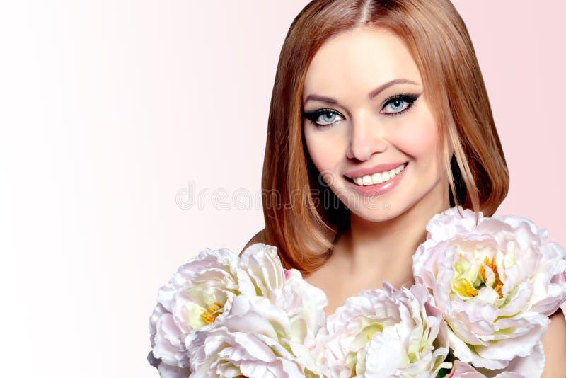 Όμορφη νέα γυναίκα χαμόγελου με τα μεγάλα λουλούδια στοκ φωτογραφία με δικαίωμα ελεύθερης χρήσης