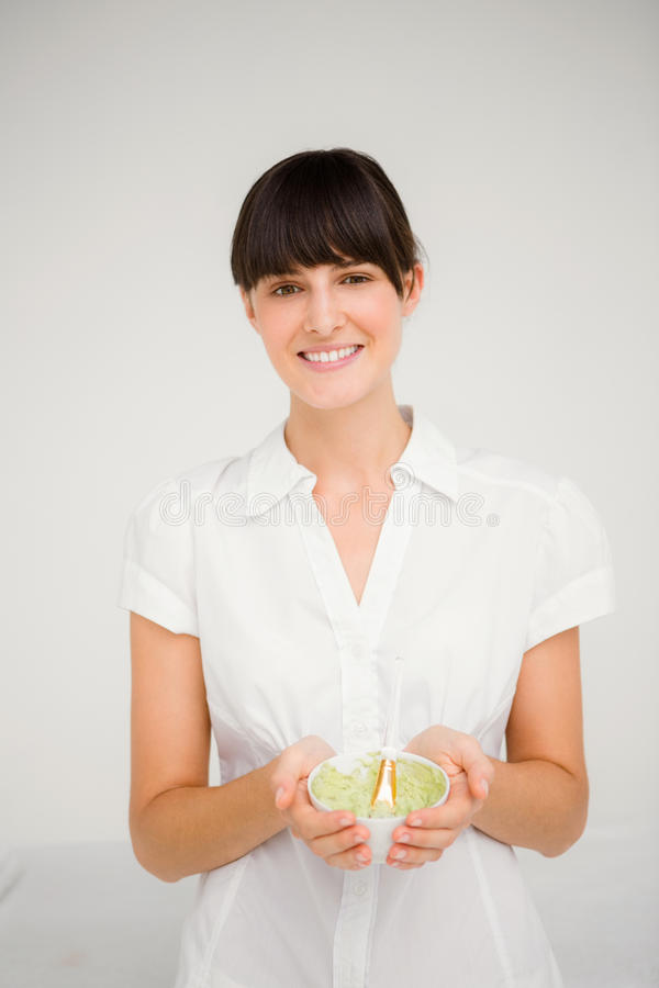 Όμορφη νέα γυναίκα brunette με την πράσινη κρέμα για να κάνει ένα μασάζ στοκ εικόνες με δικαίωμα ελεύθερης χρήσης