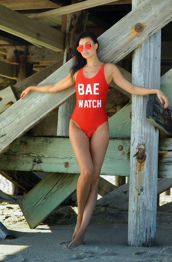 Όμορφη νέα γυναίκα brunette με το τέλειο προκλητικό κατάλληλο σώμα στην κόκκινη τοποθέτηση μαγιό στην παραλία στοκ φωτογραφίες