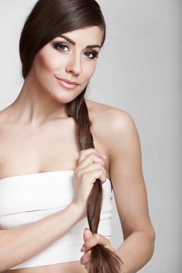 Όμορφη νέα γυναίκα brunette που κρατά την τρίχα της στοκ φωτογραφία