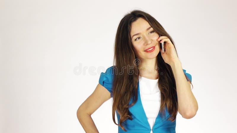 Όμορφη νέα γυναίκα brunette που μιλά στο κινητό τηλέφωνό της στο άσπρο κλίμα στοκ εικόνα
