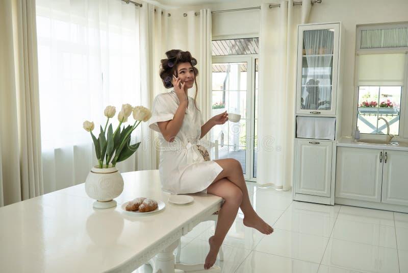 Όμορφη νέα γυναίκα brunette στα ρόλερ τρίχας που μιλά στο smartphone ενώ καθμένος στον πίνακα και έχοντας τον καφέ με στοκ φωτογραφίες