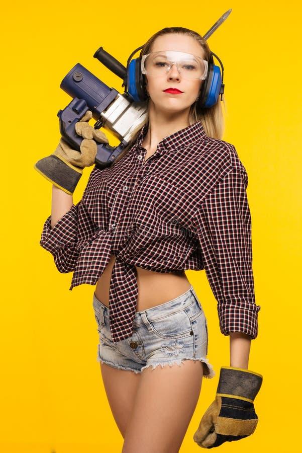 Όμορφη νέα γυναίκα perforator εκμετάλλευσης προστατευτικών διόπτρων και ακουστικών στο άξιο τρυπάνι που απομονώνεται στο κίτρινο  στοκ φωτογραφία με δικαίωμα ελεύθερης χρήσης