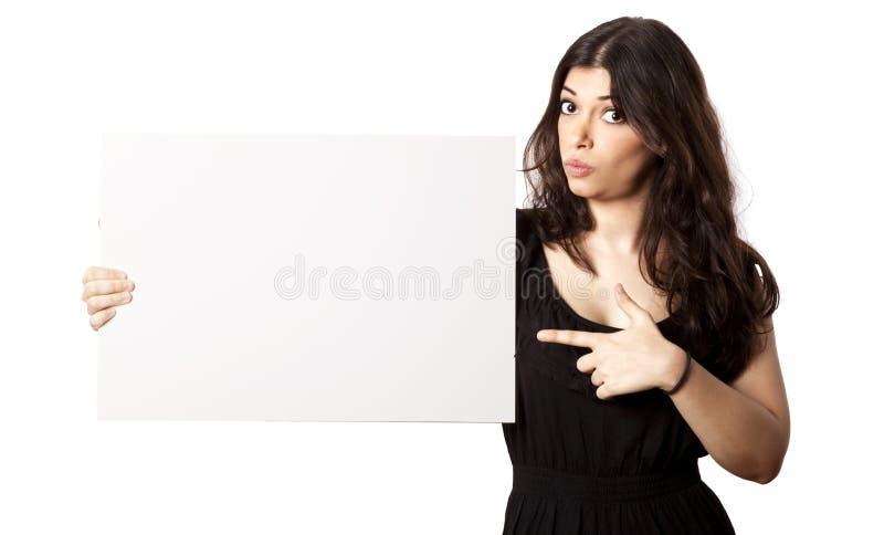 Απομονωμένη έκπληκτη γυναίκα που δείχνει στο σημάδι στοκ φωτογραφία με δικαίωμα ελεύθερης χρήσης