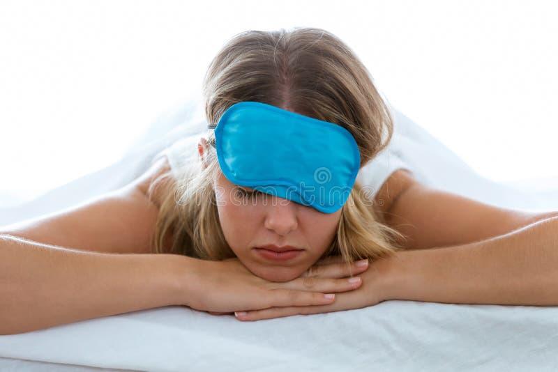 Όμορφη νέα εξαντλημένη γυναίκα με τη μάσκα ύπνου που υφίσταται την αϋπνία που προσπαθεί στον ύπνο πέρα από το άσπρο υπόβαθρο στοκ φωτογραφία με δικαίωμα ελεύθερης χρήσης