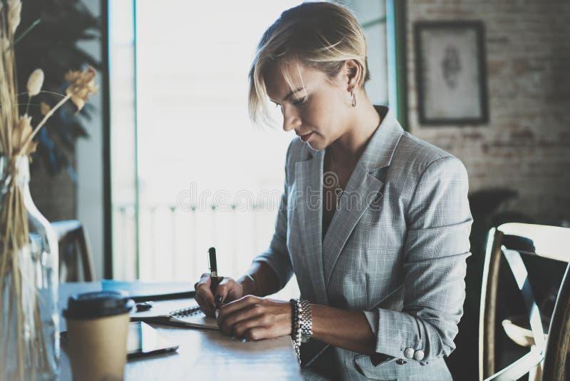 Όμορφη νέα επιχειρηματίας που γράφει κάτι στο σημειωματάριο καθμένος στην πολυθρόνα στο καθιστικό γοητευτικό θηλυκό στοκ φωτογραφία με δικαίωμα ελεύθερης χρήσης