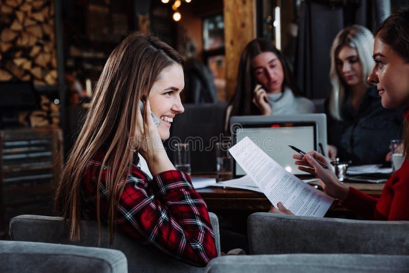 Όμορφη νέα επιχειρηματίας που μιλά στο τηλέφωνο σε έναν καφέ και ένα χαμόγελο στοκ φωτογραφία με δικαίωμα ελεύθερης χρήσης