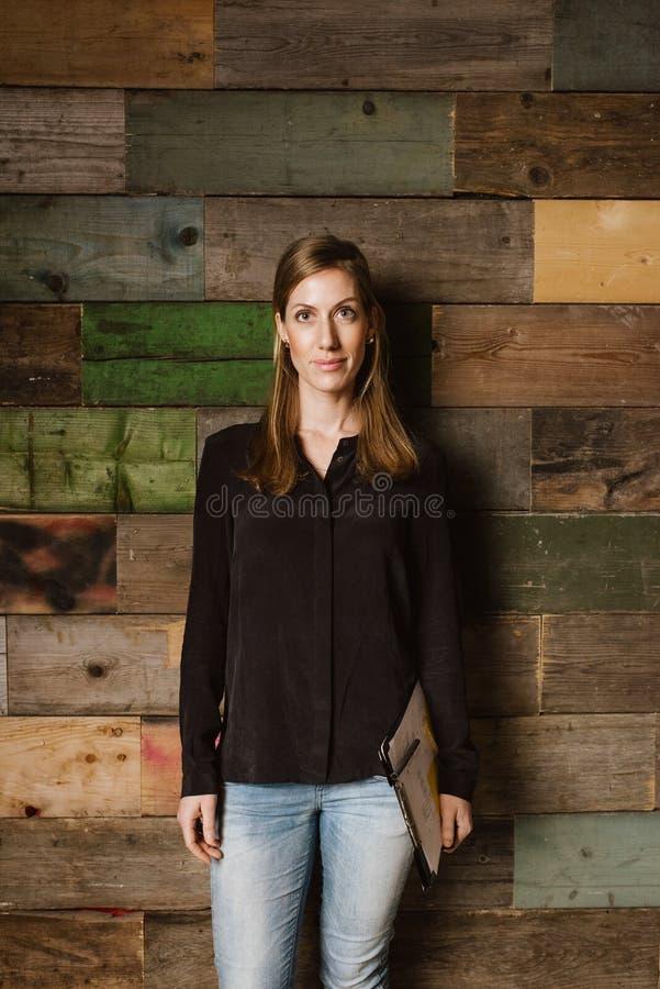 Όμορφη νέα επιχειρηματίας που στέκεται ενάντια σε έναν ξύλινο τοίχο στοκ εικόνα με δικαίωμα ελεύθερης χρήσης