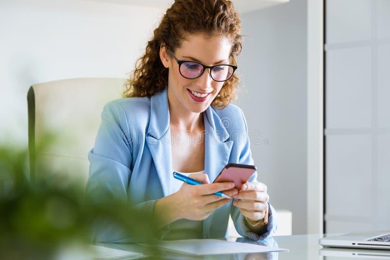 Όμορφη νέα επιχειρηματίας που χρησιμοποιεί το κινητό τηλέφωνό της στο γραφείο στοκ εικόνες