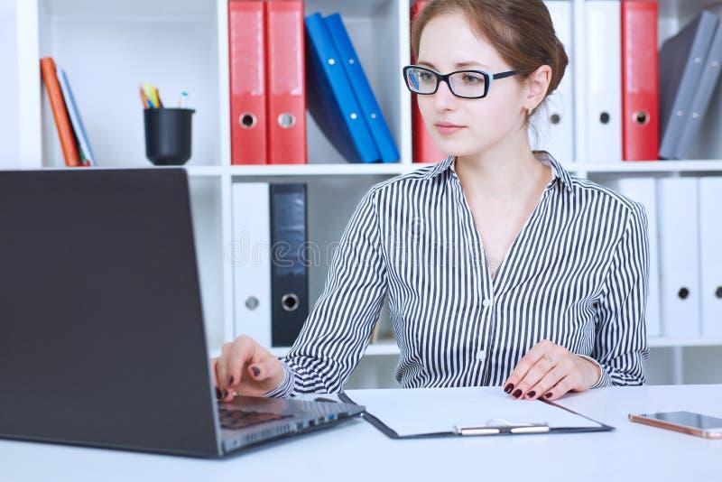 Όμορφη νέα επιχειρηματίας στα γυαλιά που λειτουργούν σε ένα lap-top στο γραφείο Επιχείρηση, αγορά ανταλλαγής, προσφορά εργασίας στοκ εικόνες