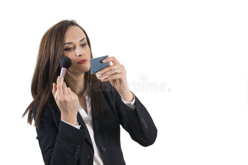 Όμορφη νέα επιχειρησιακή γυναίκα που εφαρμόζει το μάτι της makeup, απομονωμένος στοκ φωτογραφίες με δικαίωμα ελεύθερης χρήσης