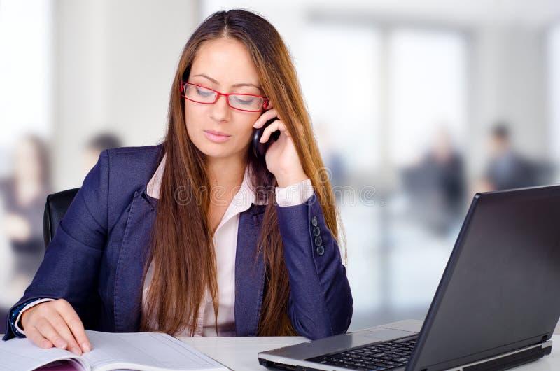 Όμορφη νέα επιχειρησιακή γυναίκα που κάνει ένα τηλεφώνημα στο γραφείο της στοκ εικόνες