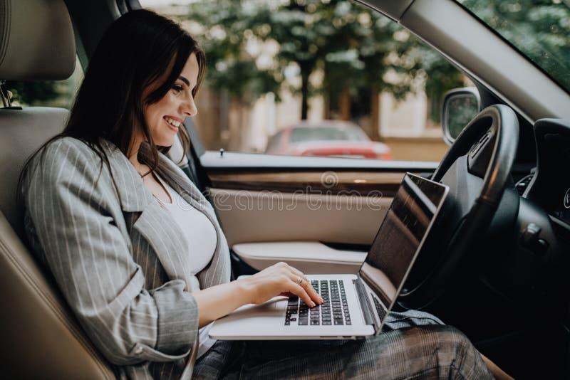 Όμορφη νέα επιχειρησιακή γυναίκα που χρησιμοποιεί το lap-top στο αυτοκίνητο στοκ φωτογραφία με δικαίωμα ελεύθερης χρήσης