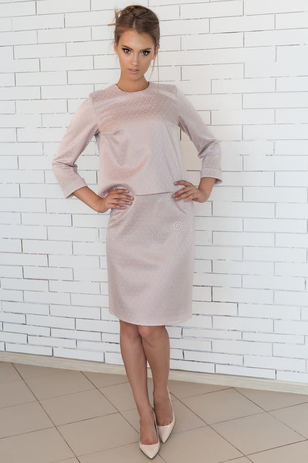 Όμορφη νέα επιχειρησιακή γυναίκα σε ένα κοστούμι επιχειρησιακού ύφους στο στούντιο κοντά στο τουβλότοιχο στοκ εικόνες με δικαίωμα ελεύθερης χρήσης