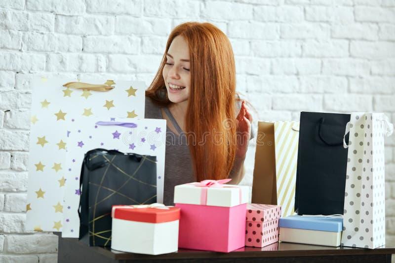 Όμορφη νέα ευτυχής γυναίκα με τις τσάντες αγορών που κάθεται στον πίνακα στοκ εικόνες