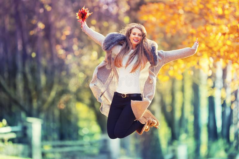 Όμορφη νέα ευτυχής γυναίκα που πηδά στο πάρκο φθινοπώρου στοκ φωτογραφίες