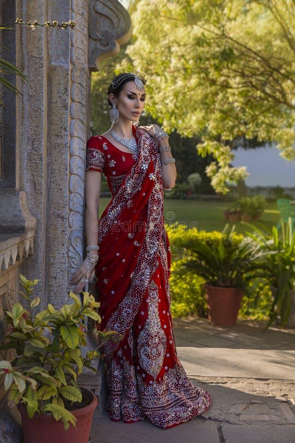 Όμορφη νέα ινδική γυναίκα στον παραδοσιακό ιματισμό με νυφικό στοκ εικόνες