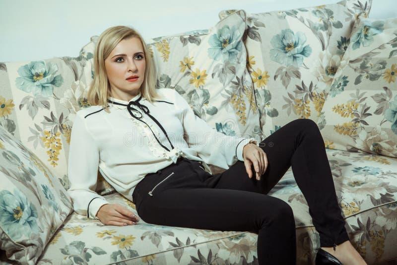 Όμορφη νέα καυκάσια ξανθή πρότυπη τοποθέτηση μόδας στον καναπέ στοκ εικόνα