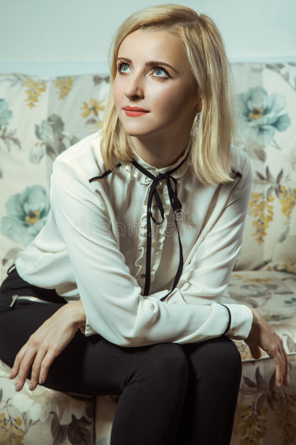 Όμορφη νέα καυκάσια ξανθή πρότυπη τοποθέτηση μόδας στον καναπέ στοκ εικόνες με δικαίωμα ελεύθερης χρήσης