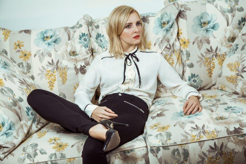 Όμορφη νέα καυκάσια ξανθή πρότυπη τοποθέτηση μόδας στον καναπέ στοκ φωτογραφία με δικαίωμα ελεύθερης χρήσης