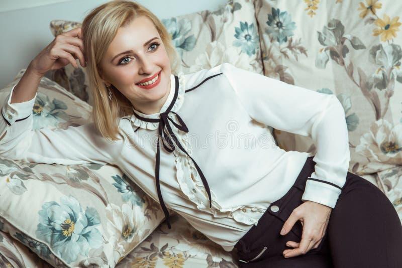 Όμορφη νέα καυκάσια ξανθή πρότυπη τοποθέτηση μόδας στον καναπέ στοκ φωτογραφία