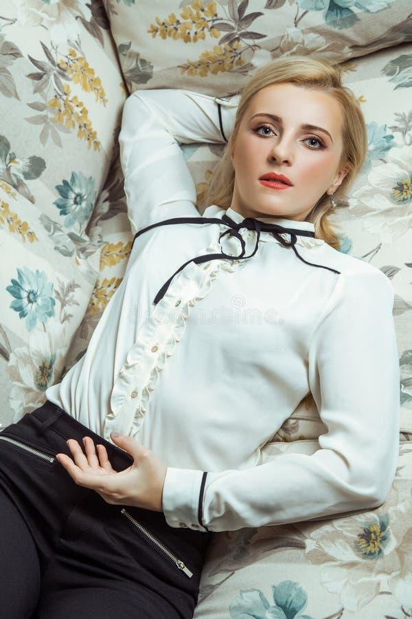 Όμορφη νέα καυκάσια ξανθή πρότυπη τοποθέτηση μόδας στον καναπέ στοκ φωτογραφίες