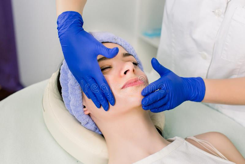 Όμορφη νέα καυκάσια χαλάρωση γυναικών με μασάζ και cosmetology προσώπου τις διαδικασίες beauty spa στοκ εικόνα με δικαίωμα ελεύθερης χρήσης