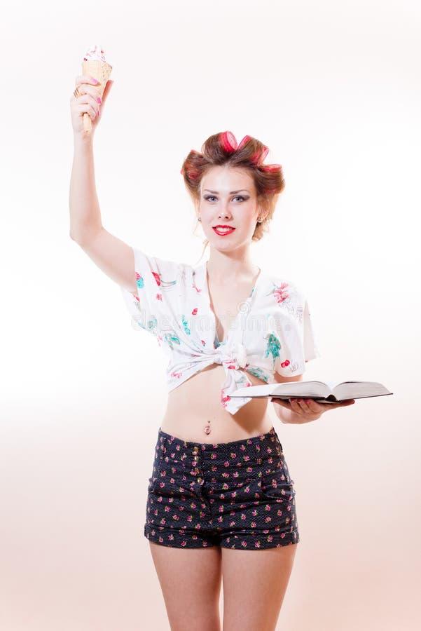 Όμορφη νέα κομψή γυναίκα με την τοποθέτηση παγωτού και βιβλίων ως άγαλμα της ελευθερίας που φαίνεται κεκλεισμένων των θυρών που α στοκ φωτογραφίες με δικαίωμα ελεύθερης χρήσης