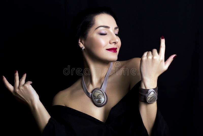Όμορφη νέα κομψή γυναίκα σε ένα μοντέρνο μαύρο φόρεμα στοκ εικόνα