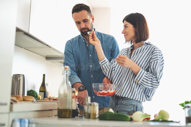 Όμορφη νέα κυρία που προσπαθεί να ταΐσει το σοβαρό φίλο με το κρεμμύδι στοκ φωτογραφίες με δικαίωμα ελεύθερης χρήσης