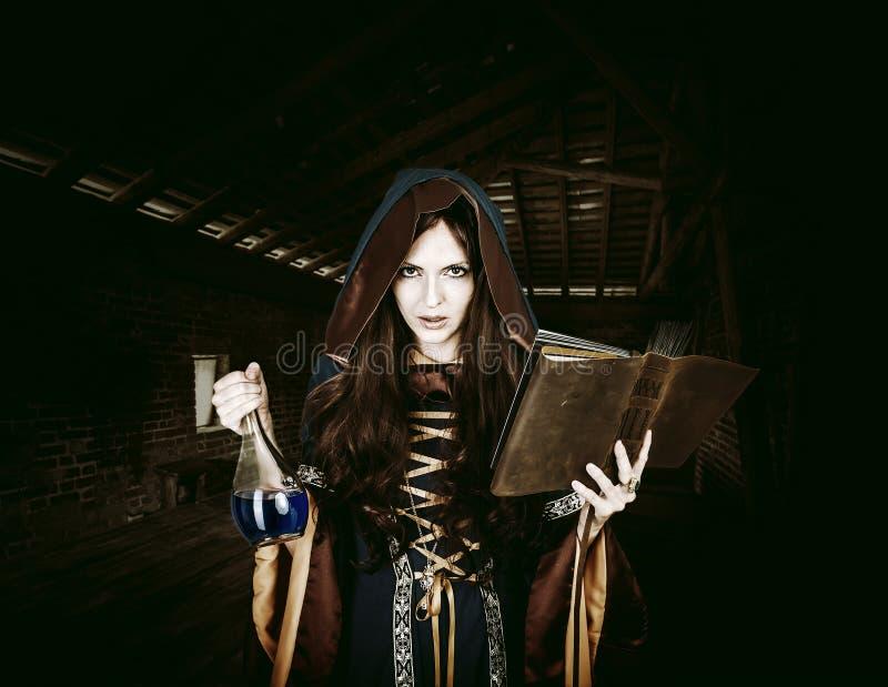 Όμορφη νέα μάγισσα αποκριών που κρατά το μαγικά βιβλίο και το δηλητήριο στοκ εικόνες