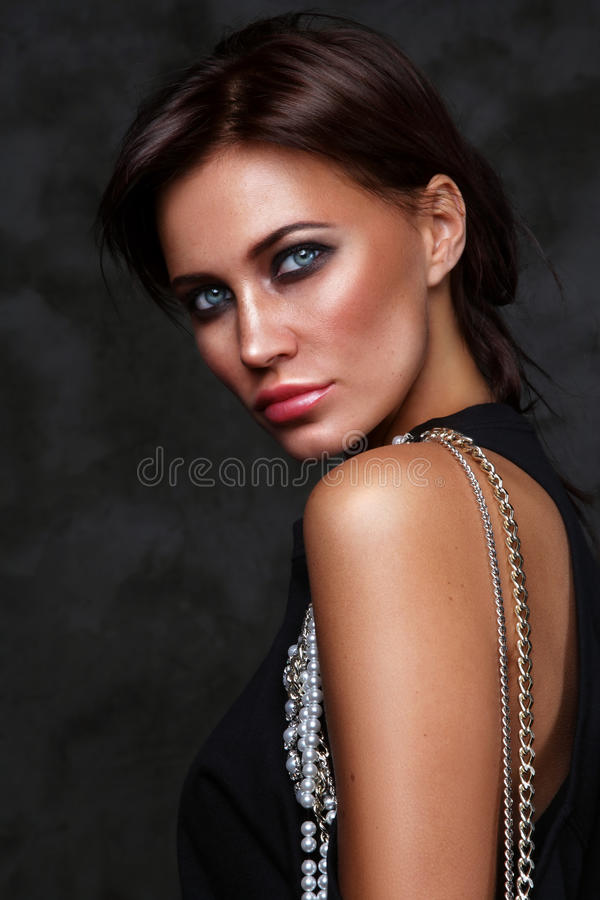 Όμορφη νέα μαυρισμένη γυναίκα με την καπνώή σύνθεση ματιών στοκ φωτογραφία