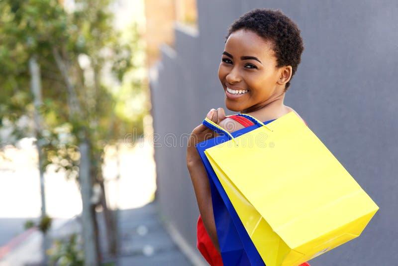 Όμορφη νέα μαύρη γυναίκα που χαμογελά με τις τσάντες αγορών έξω στοκ φωτογραφία με δικαίωμα ελεύθερης χρήσης