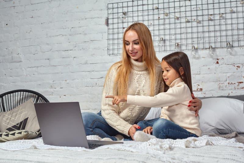 Όμορφη νέα μητέρα και η χαριτωμένη κόρη της στα άσπρα πουλόβερ και τα τζιν που βρίσκονται στο κρεβάτι στο σπίτι, το γέλιο και το  στοκ εικόνες με δικαίωμα ελεύθερης χρήσης
