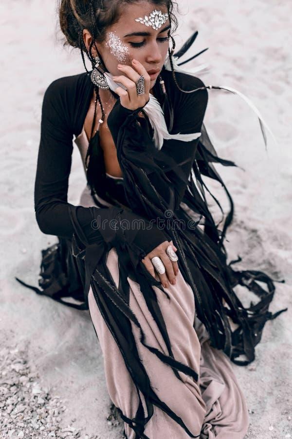 Όμορφη νέα μοντέρνη συνεδρίαση γυναικών ύφους boho στο beac στοκ εικόνες
