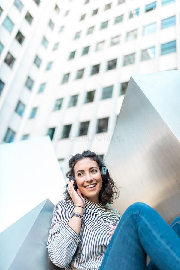 Όμορφη νέα μουσική ακούσματος γυναικών υπαίθρια στοκ φωτογραφία με δικαίωμα ελεύθερης χρήσης