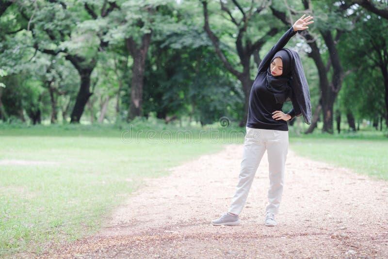 Όμορφη νέα μουσουλμανική ασιατική γυναίκα που κάνει την άσκηση πρίν τρέχει στοκ φωτογραφία με δικαίωμα ελεύθερης χρήσης
