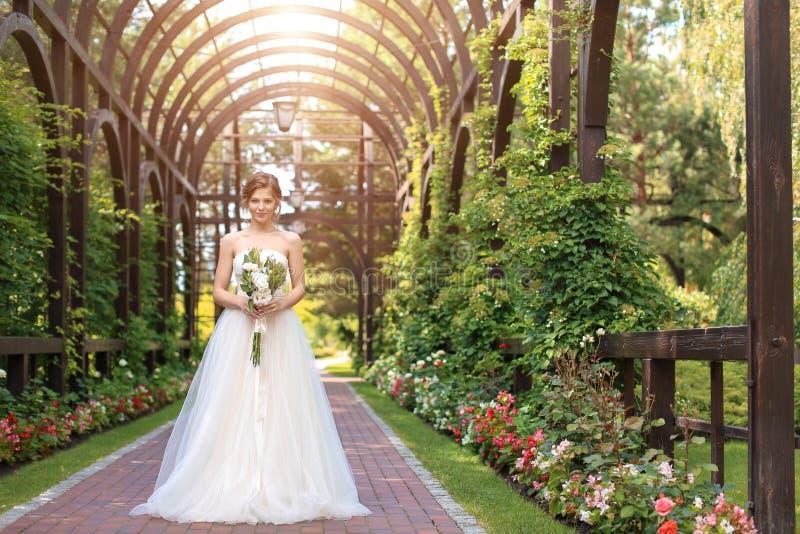Όμορφη νέα νύφη με τη γαμήλια ανθοδέσμη υπαίθρια στοκ εικόνα