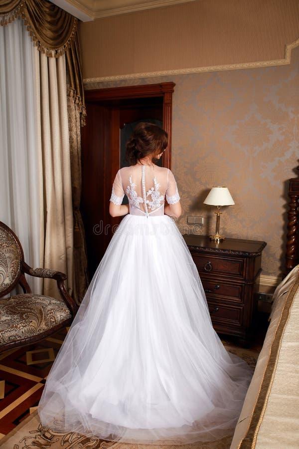 Όμορφη νέα νύφη με τις τρίχες brunette σε μια κρεβατοκάμαρα Κλασικό άσπρο γαμήλιο φόρεμα Ολόκληρο πορτρέτο, πλάτη άποψης στοκ εικόνες