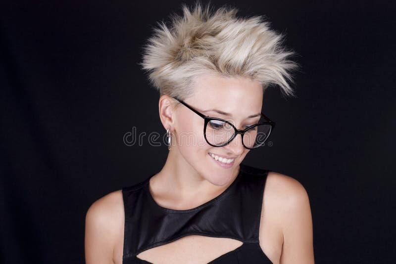 Όμορφη νέα ξανθή γυναίκα με τα γυαλιά και ένα μοντέρνο μαύρο shi στοκ φωτογραφία με δικαίωμα ελεύθερης χρήσης