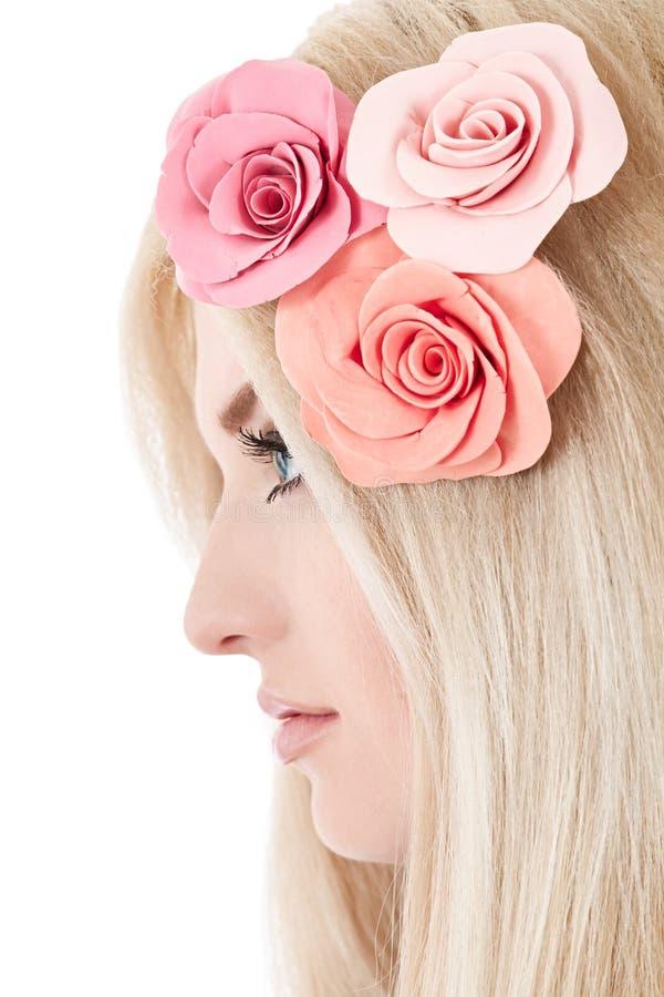 Όμορφη νέα ξανθή γυναίκα με τα τρυφερά λουλούδια στην τρίχα της στοκ εικόνα