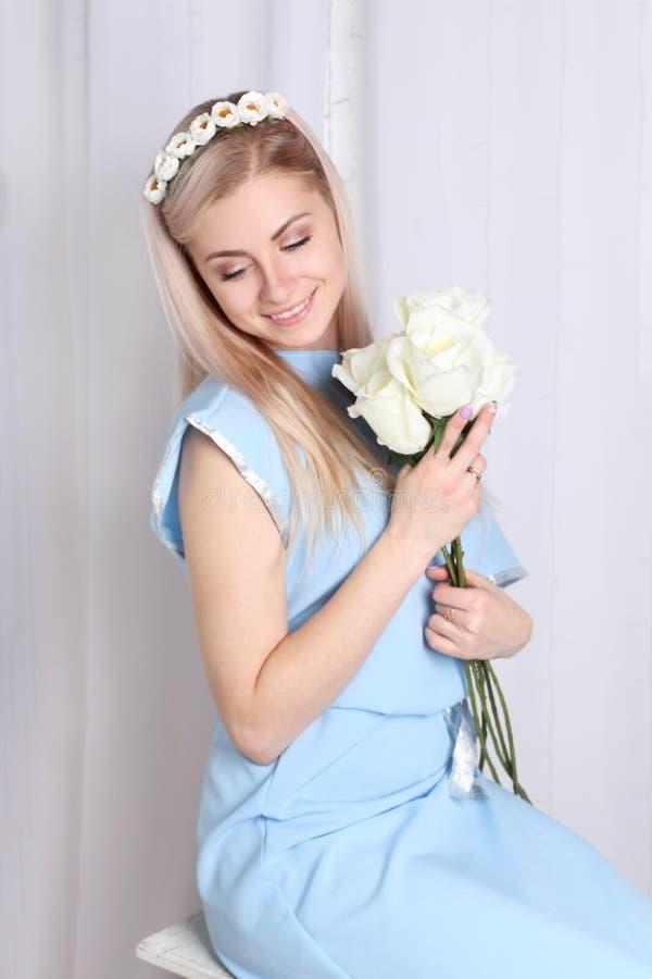 Όμορφη νέα ξανθή γυναίκα με το στεφάνι λουλουδιών στοκ φωτογραφίες