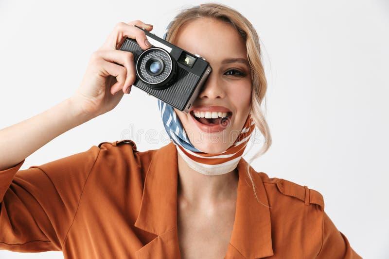 Όμορφη νέα ξανθή όμορφη γυναίκα που φορά την τοποθέτηση μαντίλι μεταξιού που απομονώνεται πέρα από την άσπρη φωτογράφιση καμερών  στοκ φωτογραφία με δικαίωμα ελεύθερης χρήσης