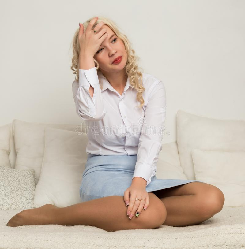 Όμορφη νέα ξανθή γυναίκα σε μια άσπρη συνεδρίαση μπλουζών σε έναν καναπέ στοκ εικόνες