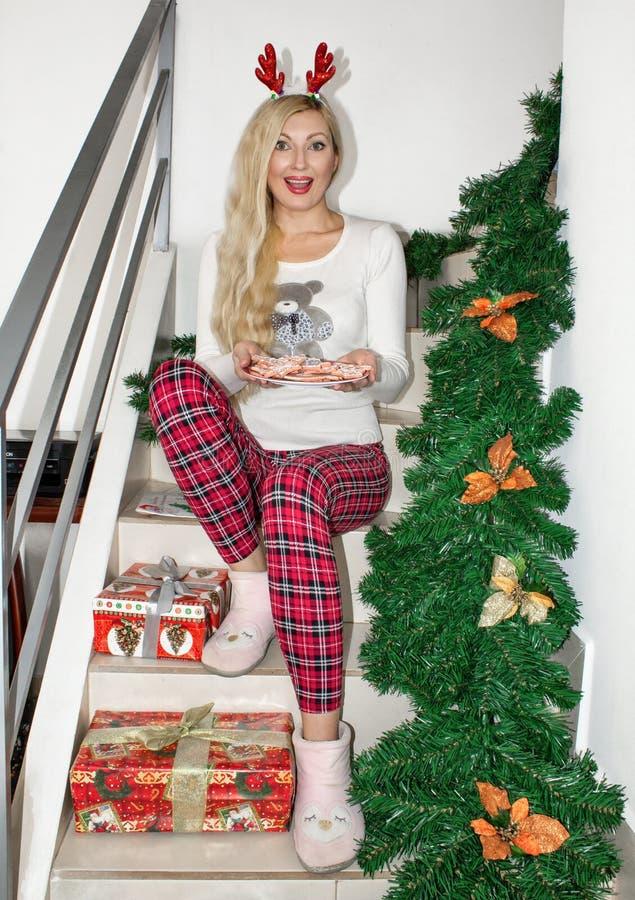 Όμορφη νέα ξανθή γυναίκα στις πυτζάμες Χριστουγέννων και με τα κέρατα ταράνδων, που κάθονται στα βήματα και που κρατούν ένα μπισκ στοκ εικόνα