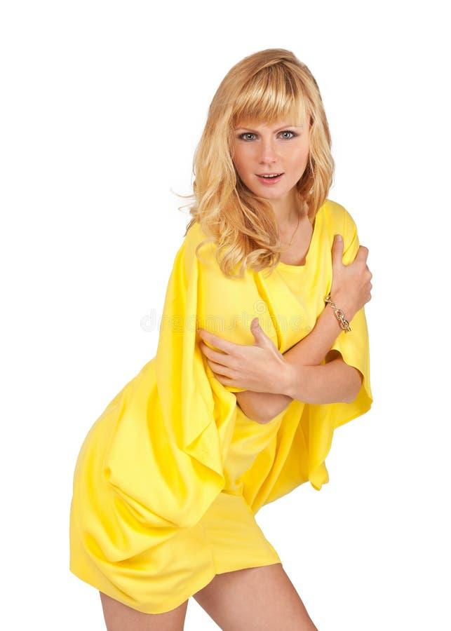 Όμορφη νέα ξανθή γυναίκα στο κίτρινο φόρεμα στοκ εικόνες