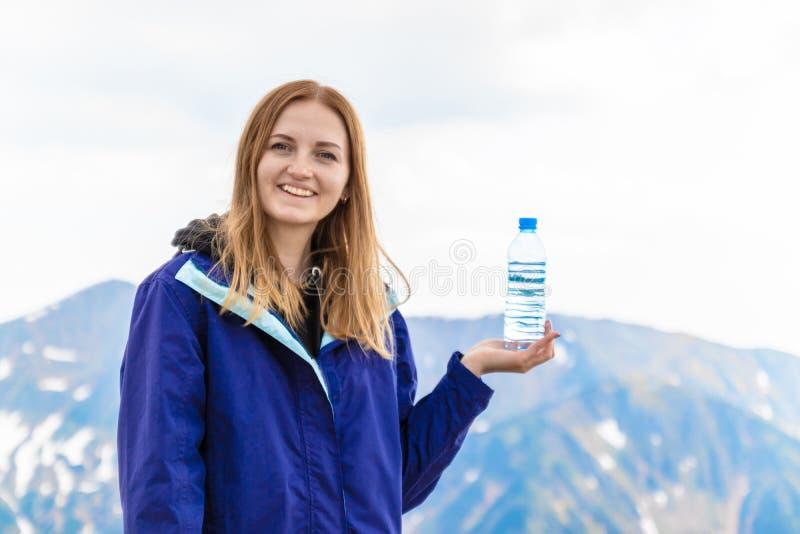 Όμορφη νέα ξανθή ευτυχής γυναίκα ταξιδιού που κρατά ένα μπουκάλι νερό στα βουνά Στηρίζεται μετά από να αναρριχηθεί στοκ φωτογραφία με δικαίωμα ελεύθερης χρήσης